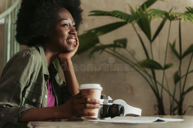 Chiuda su di giovane donna africana allegra che ha resto in self-service fotografia stock
