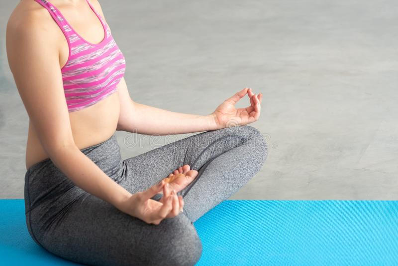 Chiuda su di giovane donna caucasica in vestiti di sport di yoga che meditano e che fanno la posizione di yoga del loto nella pos immagine stock libera da diritti