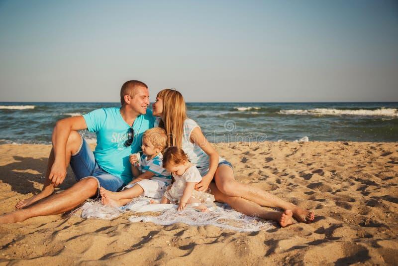 Chiuda su di giovane famiglia amorosa felice con i piccoli bambini nel medio, divertendosi alla spiaggia insieme vicino all'ocean immagini stock