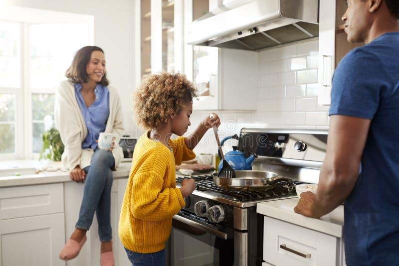 Chiuda su di giovane famiglia che spende insieme il tempo mentre preparano l'alimento nella loro cucina, fuoco selettivo fotografie stock libere da diritti