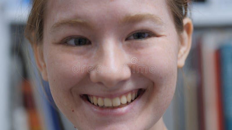 Chiuda su di giovane fronte femminile sorridente, dell'interno fotografia stock libera da diritti
