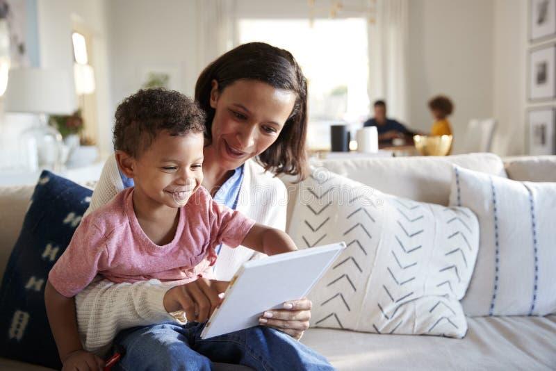 Chiuda su di giovane madre che si siede su un sofà nel salone con il suo bambino sul suo ginocchio, leggendo lui un libro, il pad immagine stock