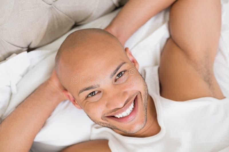 Chiuda su di giovane uomo calvo sorridente che riposa a letto fotografia stock