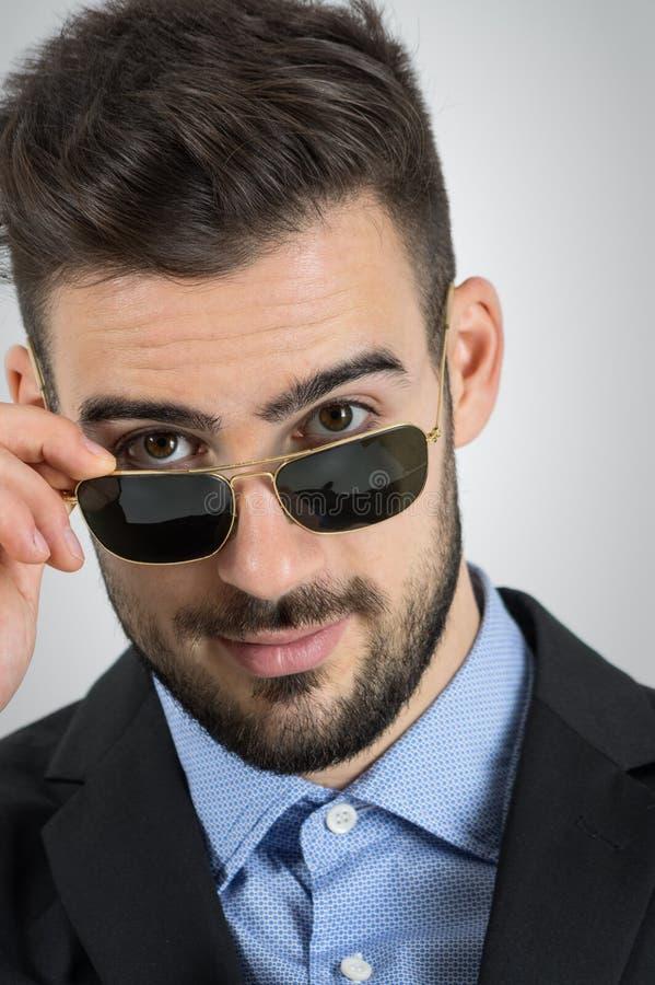 Chiuda su di giovane uomo di flirt che esamina gli occhiali da sole fotografie stock