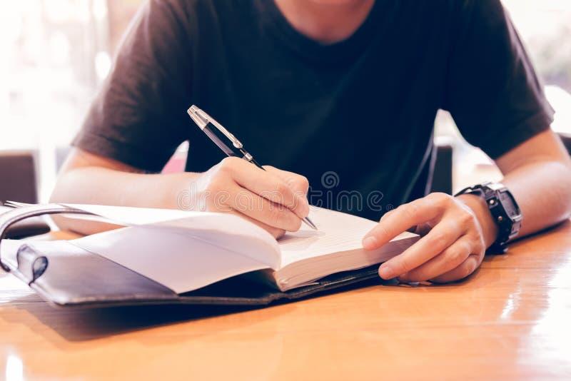 Chiuda su di giovani note di scrittura della mano nella stanza di studio fotografia stock