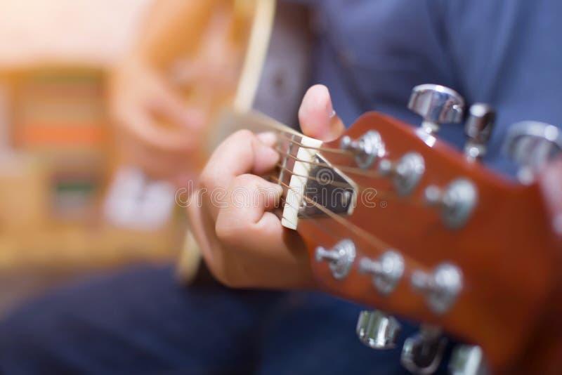 Chiuda su di giovani pantaloni a vita bassa che la donna ha praticato la chitarra nel parco, felice e goda di di giocare la chita fotografie stock