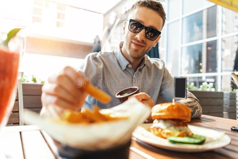 Chiuda su di giovani patate fritte ed hamburger mangiatori di uomini attraenti al caffè della via immagine stock libera da diritti