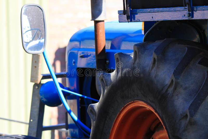 Chiuda su di grande gomma di vecchio trattore antico antico blu con lo specchietto retrovisore ed il motore su un'azienda agricol immagine stock libera da diritti