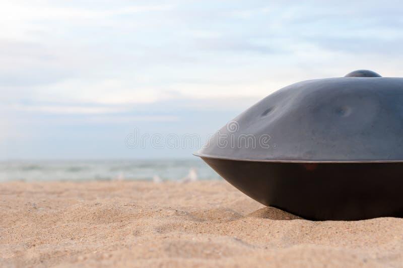 Chiuda su di handpan o di caduta con il mare e la spiaggia su fondo La caduta è strumento musicale etnico tradizionale del tambur immagini stock