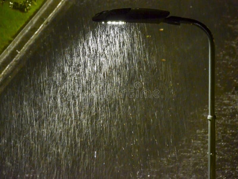 Chiuda su di iluminazione pubblica con pioggia torrenziale fotografia stock libera da diritti