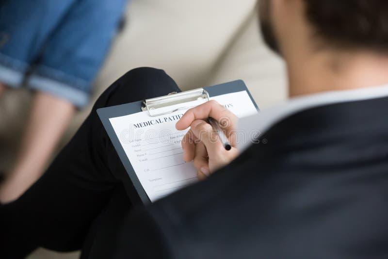 Chiuda su di informazioni di riempimento di medico maschio in carta medica immagine stock libera da diritti