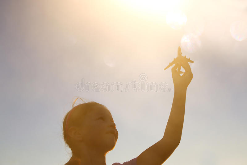 chiuda su di kid& x27; aeroplano del giocattolo della tenuta della mano di s contro il cielo di tramonto immagini stock libere da diritti