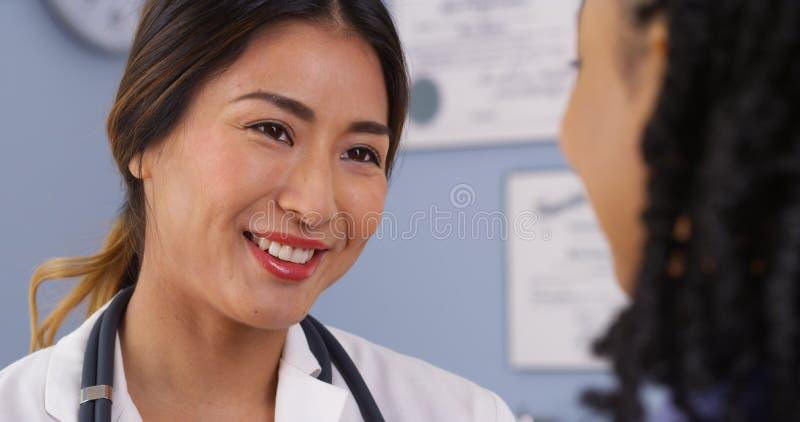 Chiuda su di medico asiatico felice che esamina il paziente fotografia stock