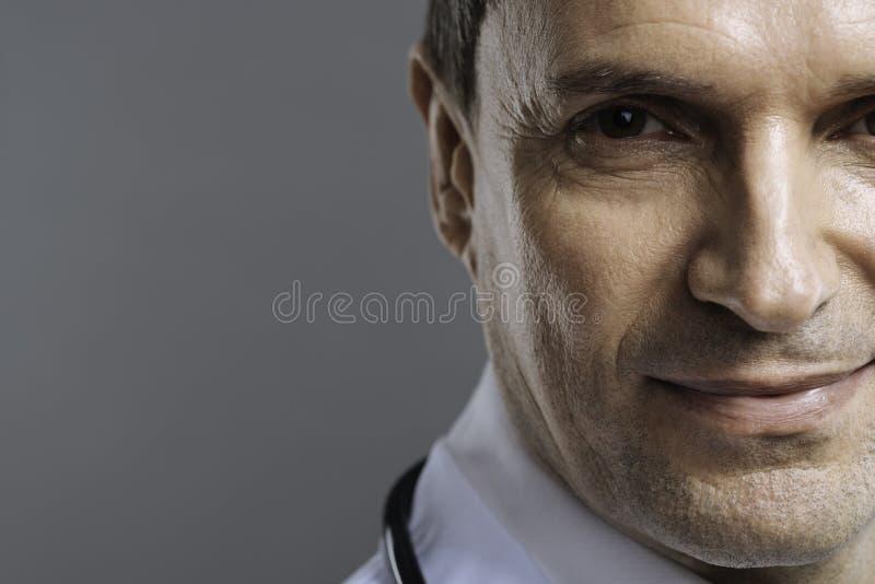 Chiuda su di medico bello che sorride su un fondo grigio immagine stock libera da diritti