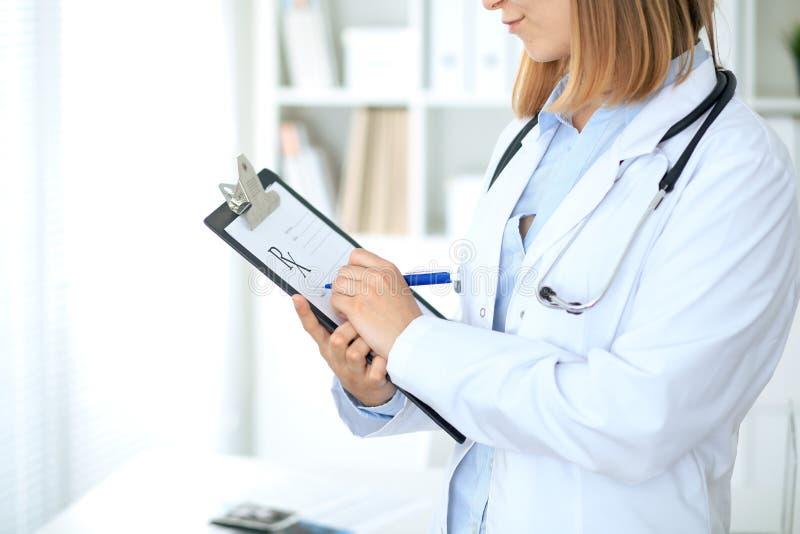 Chiuda su di medico femminile che scrive una prescrizione medica alla lavagna per appunti mentre stanno fotografia stock