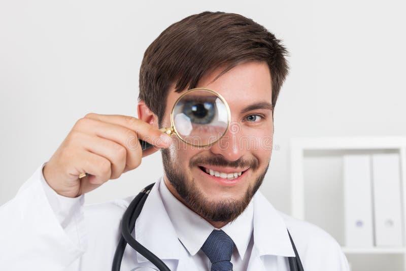 Chiuda su di medico sorridente con la lente d'ingrandimento fotografia stock