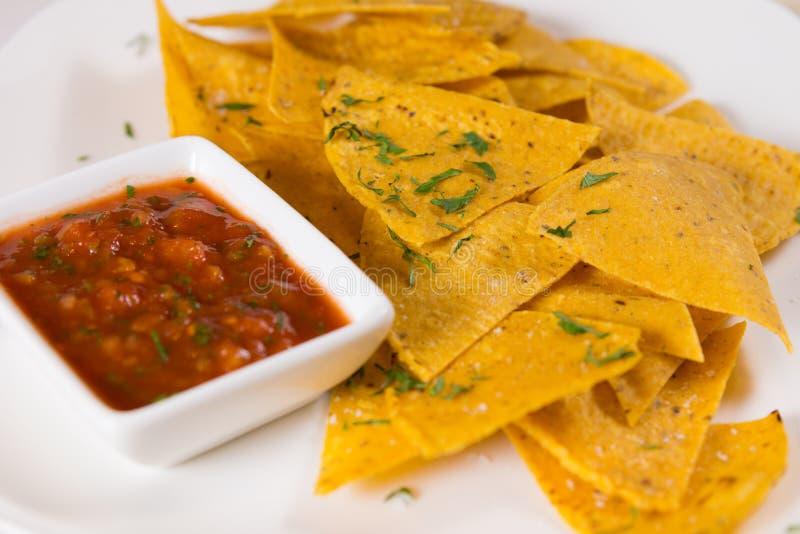 Chiuda su di Nacho Chips con salsa immagini stock libere da diritti