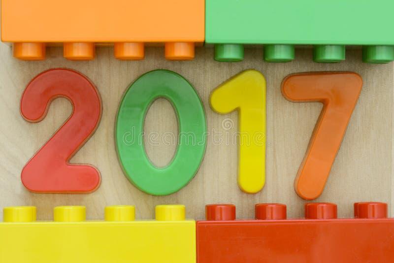 Chiuda su di 2017 numeri piani della plastica con i blocchetti di plastica del giocattolo che incorniciano sul fondo di legno immagine stock libera da diritti