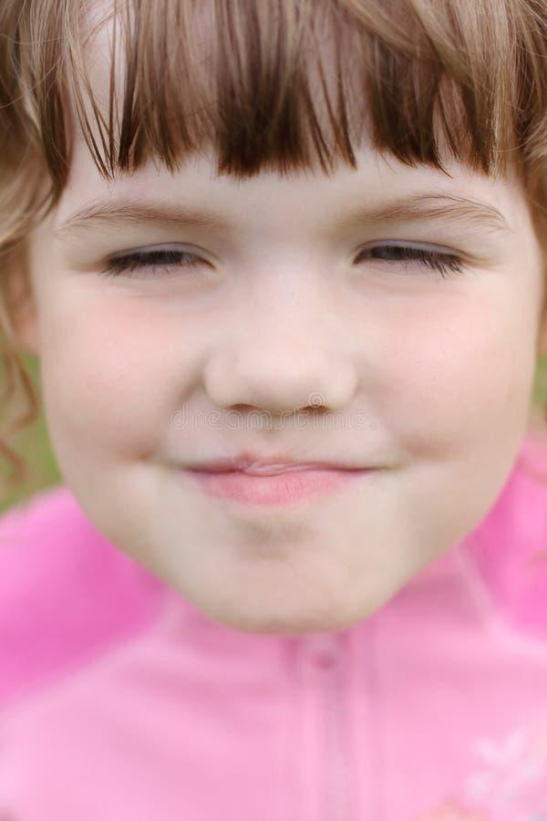 Chiuda su di piccola bella ragazza facente smorfie felice del fronte fotografia stock