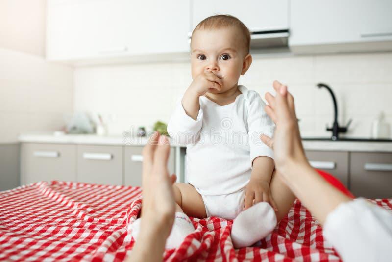Chiuda su di piccolo neonato allegro con i grandi occhi e mano marroni in bocca che esamina la madre mentre lei che tira le mani  fotografia stock libera da diritti