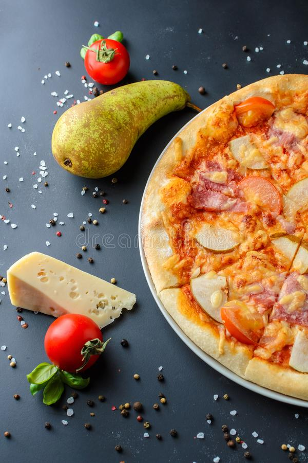 Chiuda su di pizza hawaiana con la pera su un fondo scuro immagine stock