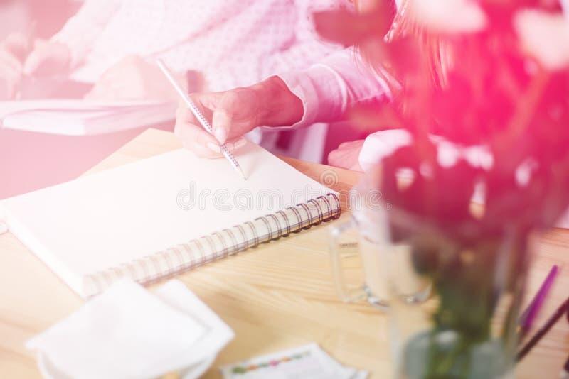 Chiuda su di scrittura nell'organizzatore, tonalità leggera della mano del ` s della donna fotografia stock