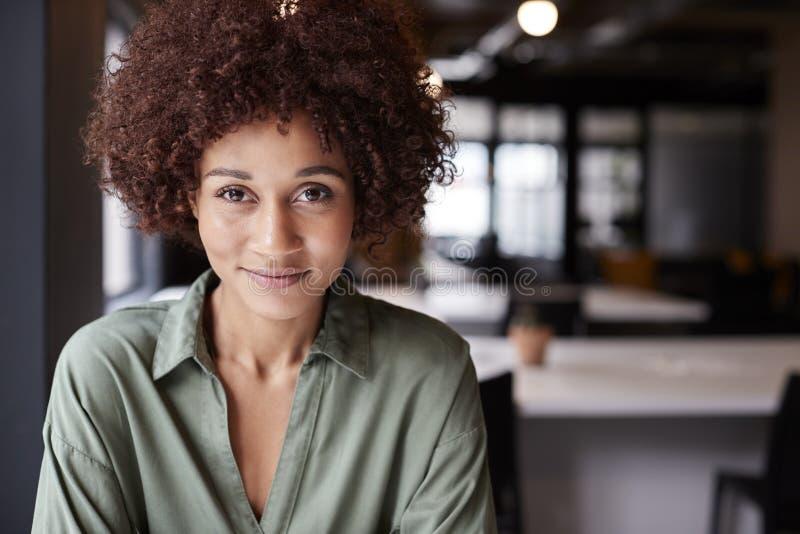 Chiuda su di seduta creativa femminile nera millenaria in un ufficio open space che sorride alla macchina fotografica immagine stock