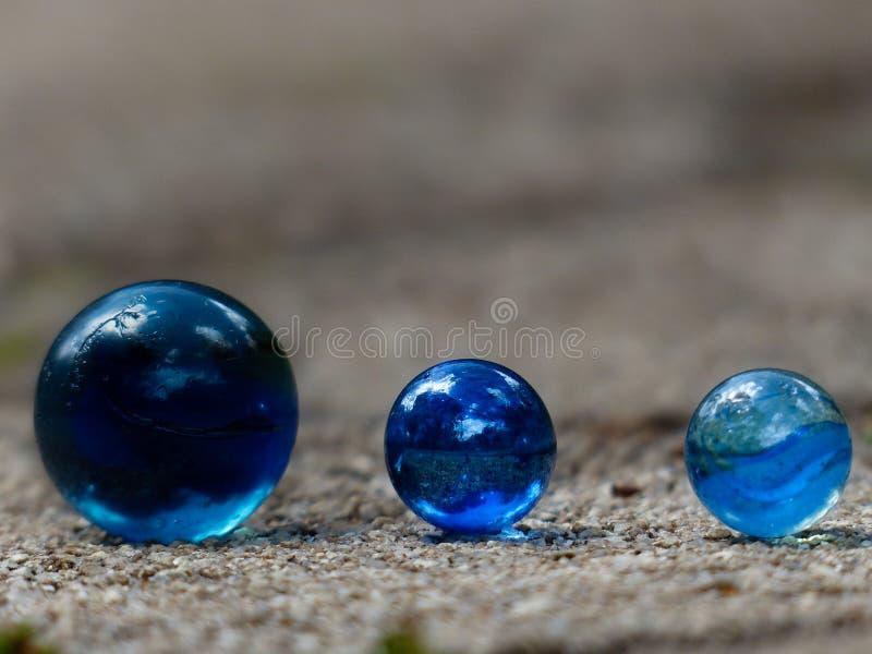 Chiuda su di tre marmi di vetro blu in una fila con lo spazio vago del fondo per disporre il testo fotografia stock