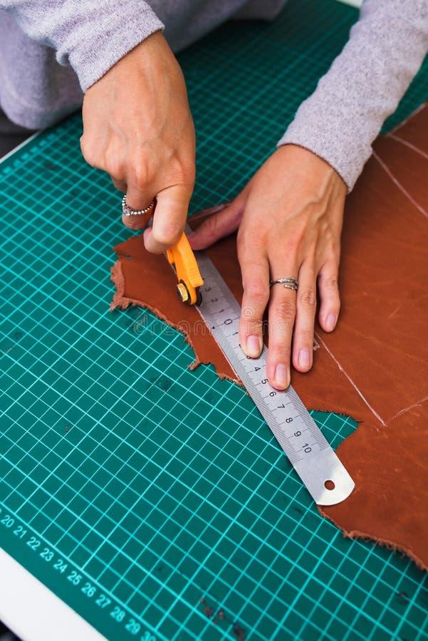 Chiuda su di un artigiano che lavora con il cuoio nel suo laboratorio fotografia stock libera da diritti