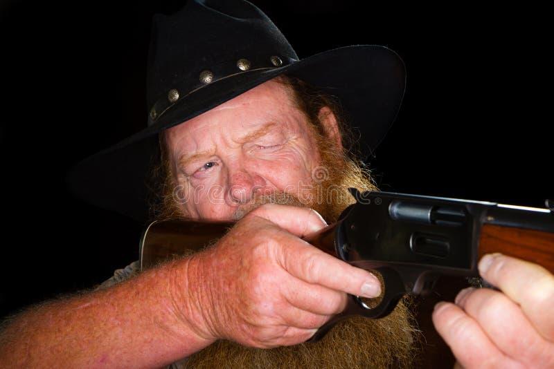 Chiuda su di un cowboy più anziano circa per tirare l'innesco immagini stock
