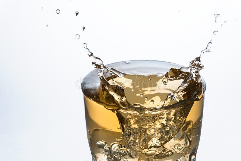 Chiuda su di un cubetto di ghiaccio che spruzza su un vetro di Ginger Ale fotografie stock