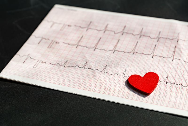 Chiuda su di un elettrocardiogramma sotto forma di documento il cuore di legno rosso VI Carta di elettrocardiogramma o di ECG su  fotografie stock