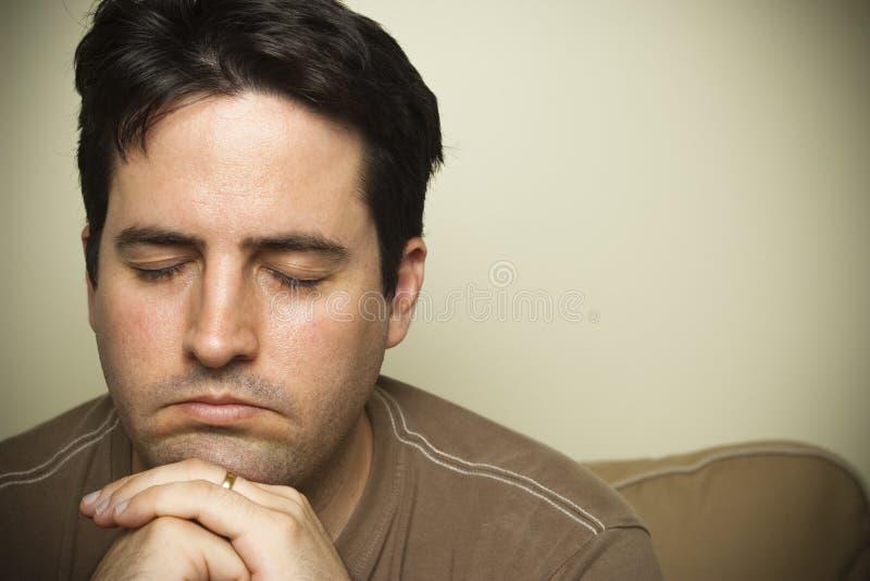 Chiuda su di un giovane nella preghiera immagini stock libere da diritti