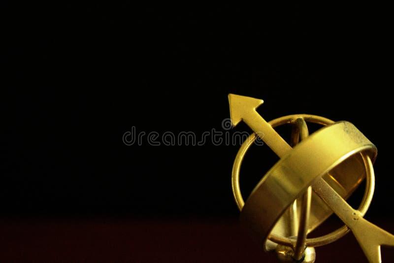 Chiuda su di un globo dorato d'annata dell'astrolabio nell'oscurità fotografia stock libera da diritti