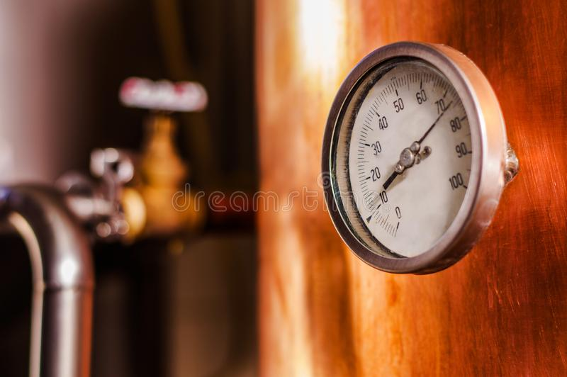 Chiuda su di un manometro dentro di una fabbrica di birra moderna della pianta della birra con le navi, le vasche ed i tubi fatti immagine stock libera da diritti