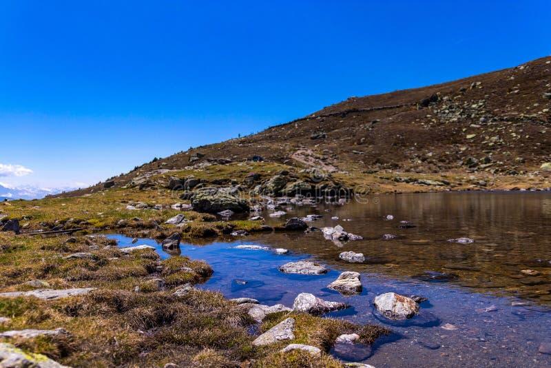Chiuda su di un pendio di collina accanto ad una massa di acqua fotografie stock libere da diritti