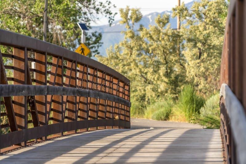 Chiuda su di un ponte con la piattaforma legna del guardavia del metallo e un giorno soleggiato immagine stock