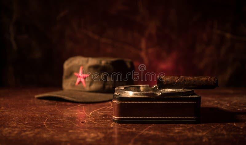 Chiuda su di un sigaro e di un portacenere cubani sulla tavola di legno Tavola comunista di comandante del dittatore nella stanza immagini stock libere da diritti
