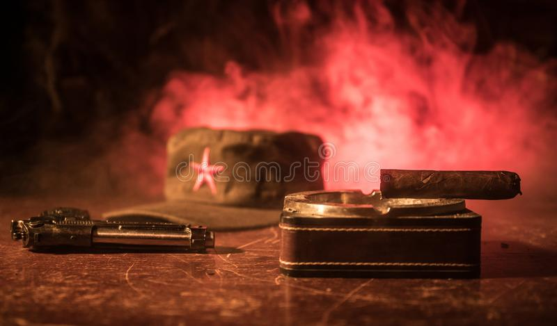 Chiuda su di un sigaro e di un portacenere cubani sulla tavola di legno Tavola comunista di comandante del dittatore nella stanza immagine stock libera da diritti