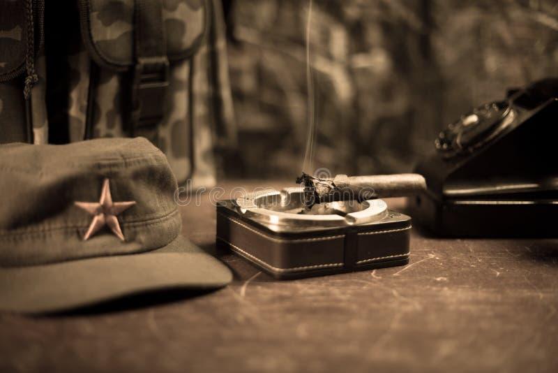 Chiuda su di un sigaro e di un portacenere cubani sulla tavola di legno Tavola comunista di comandante del dittatore nella stanza fotografie stock libere da diritti