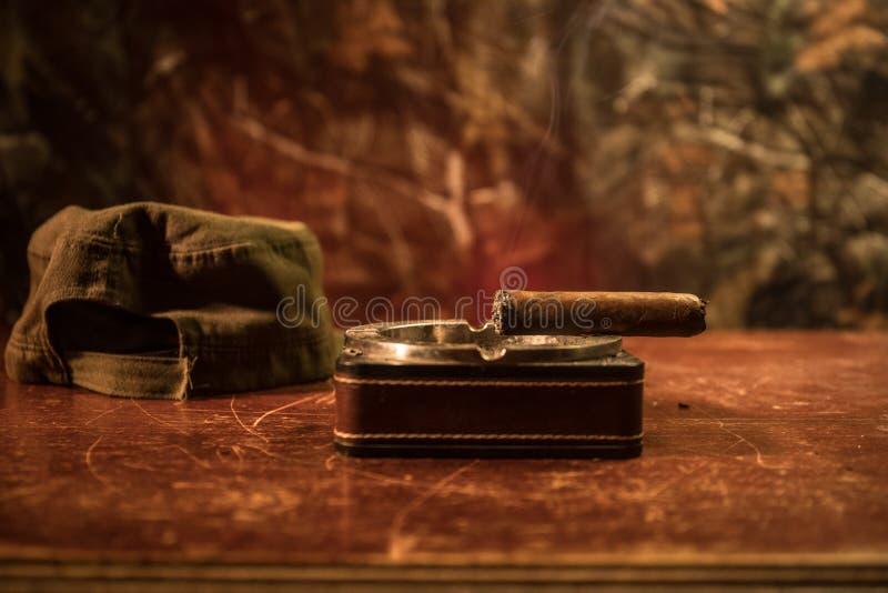 Chiuda su di un sigaro e di un portacenere cubani sulla tavola di legno Tavola comunista di comandante del dittatore nella stanza fotografie stock