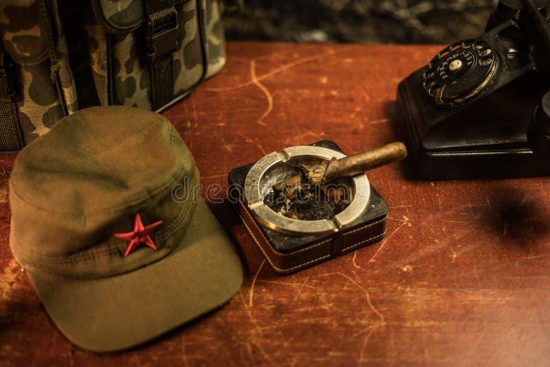 Chiuda su di un sigaro e di un portacenere cubani sulla tavola di legno Tavola comunista di comandante del dittatore nella stanza immagine stock