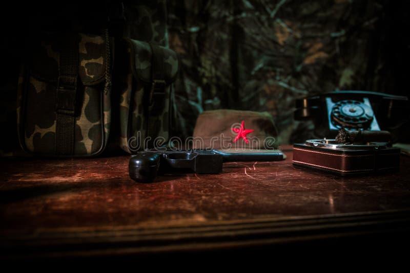 Chiuda su di un sigaro e di un portacenere cubani sulla tavola di legno Tavola comunista di comandante del dittatore nella stanza fotografia stock