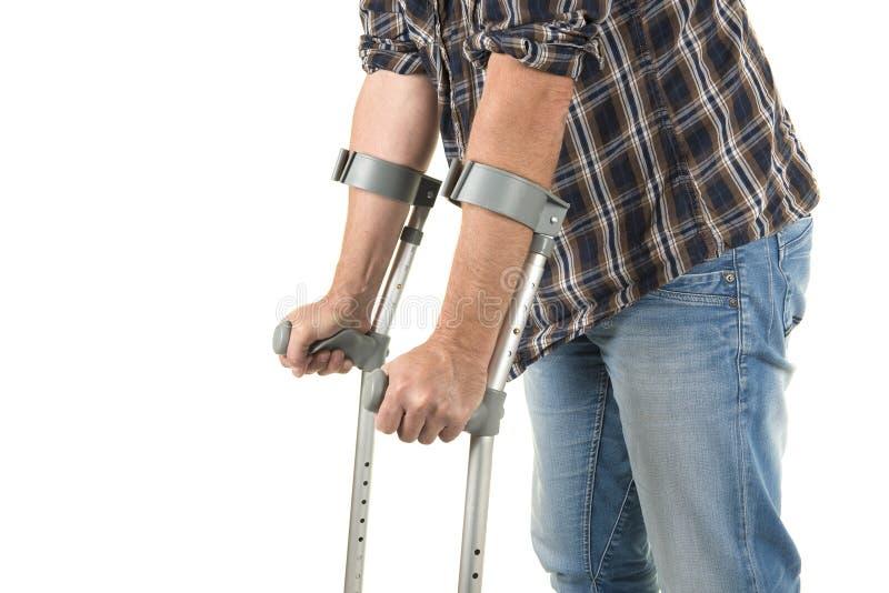 Chiuda su di un uomo che cammina con le grucce isolate su una parte posteriore bianca fotografie stock libere da diritti