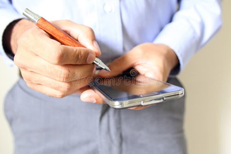 Chiuda su di un uomo che per mezzo dello Smart Phone mobile immagini stock