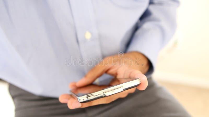 Chiuda su di un uomo che per mezzo dello Smart Phone mobile fotografie stock