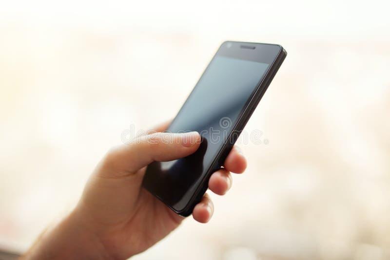 Chiuda su di un uomo che per mezzo dello Smart Phone mobile fotografie stock libere da diritti