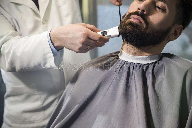 Chiuda su di un uomo d'affari dai capelli marrone serio che fa la sua pettinarsi barba e sistemato in un negozio di barbiere immagini stock