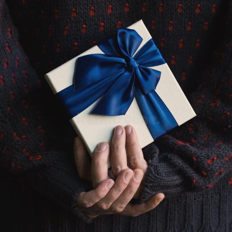 Chiuda su di un uomo in maglione che tiene un regalo con il beh del nastro blu immagini stock libere da diritti