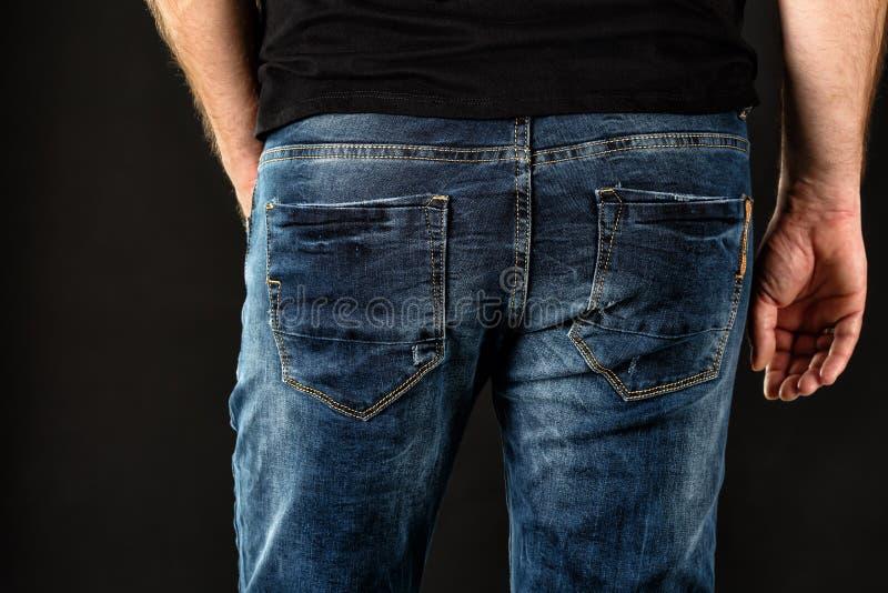 Chiuda su di un uomo piacevole per intromettersi i jeans blu scuro e la camicia nera contro fondo nero Modo maschio casuale fotografie stock libere da diritti